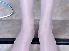 Frisky damsel unbuckles her strappy sandals to showcase her slender nyloned feet