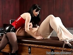 Miss Mina treats her slave to an encasement tube which forms a cocoon like casing around his body, and laces him down to the bondage bed with rope overtop of the encasement tube. Then she flogs his body and teases him with a violet wand through the encasement tube. Finally she smothers him as she beats on his cock, denying him access to anything other than the smell of her pussy.