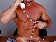 Mature fag bodybuilder Anthony Lopez getting on top of his office desk to stroke his rock-hard erection