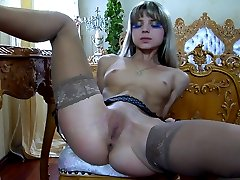 Pretty babe licks her glass toy before spreading nyloned legs for solo anal