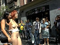 Innocent Lilyan Red is shamed around the streets of Madrid. First she's chained to a storm drain and made to drink from a dog bowl in a busy shopping street. She shows off her shaved pussy to everyone passing by. Then she's tied around a flagpole by her pigtails at a major tourist attraction. Sandra Romain leaves her on display and humiliates her in front of all the tourists. At the end of the day she's brought to an underground club where she eats pussy, sucks cock, gets fucked hard and gets her pussy pumped, in front of a bar full of gawkers.