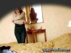 Beautiful Russianredhead filmed on a voyeur cam while disrobing near a bed