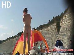 Russian nudist babe and her boyfriend sunbathe on beach