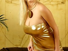 Raylene Richards posing in a gold sundress and black stockings