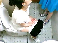 două drăguț fete asiatice reperat pe o toaleta cam pipi