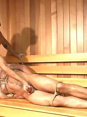 Aarin Asker's cruising in the gym when he comes across Jessie Colter taking a steamy shower. Jessie notices the curious stud groping his crotch and makes his way over to the lockers slowly, sizing Aarin up. The two start making out and exploring each others cocks when Jessie decides to make the showers steamier. Pulling rope from his locker, Jessie secures Aarin across the bench, legs spread wide. Aarin moans in the rope harness as Jessie strips the clothes from his ripped body, licking his feet and slowly moving toward his crotch. Jessie repeatedly teases Aarin's throbbing cock, bringing it so close to the edge again and again with his hands, mouth and vibrating cock sheath. Jessie moves his attention to Aarin's hole, finding it eager and hungry. Aarin takes a full fist in his ass as he begs to cum. Not yet finished, Jessie brings Aarin into the sauna and continues the edging, each one more tormenting than the last. Aarin begs to cum through a ball gag as his cock receives a massage from two hitachis. For all he's taken today, Jessie finally decides to grant Aarin an orgasm and milks out a rich load from stud. Just as Aarin moans in relief, he feels the pain of an apple polishing before he's left in a cumdrunk daze.