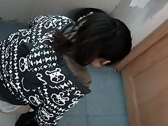 an Asian gal in a jumper urinating in public toilet for absolute ages