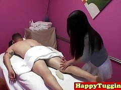 Asian massagist with tattoos jerking