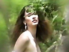 bruneta se dezbraca clipește în iarba înaltă în aer liber