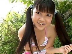 Cute Korean school student poses in bathing suit in the garden