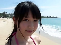 Slender Asian girl Tsukasa Arai walks on a sandy beach under the sun