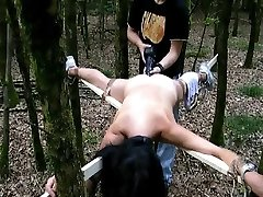 Bound to a cross and fucked with a big faux-cock in the woods