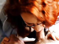 Redhead with glasses giving head