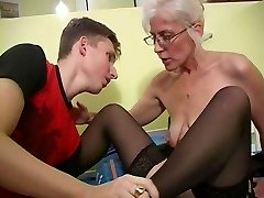 Mature with Platinum Hair Glasses and Tights Wakes the Boy
