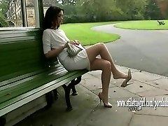 Όμορφο κορίτσι δείχνει μακριά μεταξένια λεία νάυλον πόδια και σικ ψηλά τακούνια