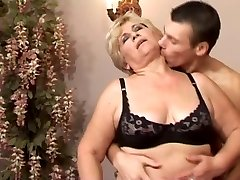 Slim Platinum-blonde 50+ with young man in couch