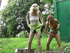 Fair gals in minis make a pee outdoors