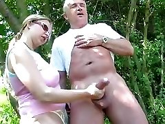 Mature duo outdoors and she gives him a handjob of the penis