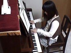Piano educator rear screws his pupil across the piano keys