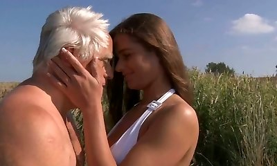 Charming busty teenager in white bikini fucks an aged fellow in the field