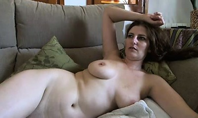 Busty mature brunette with good-sized boobs and hairy vag strips