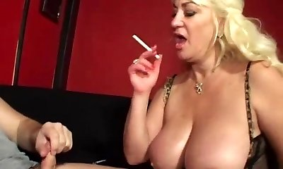Huge-chested mommy gives blowjob and smokes cigarette