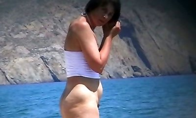 Hot mature beach nudist undresses of her clothes and gets moist