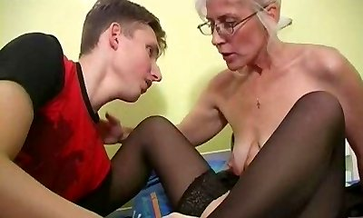 Mature with Platinum Hair Glasses and Pantyhose Wakes the Boy