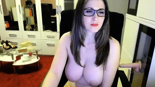 Alluring brunette with glasses exposes her big hooters for