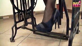 Pretty girl wearing high heels Petra sews on the sewing machine
