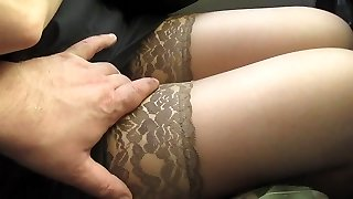 Touching her gams in tan stocking in a bus