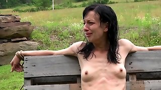 Anorexic brown-haired hussy gets her slim body corded up to wooden fence outdoors