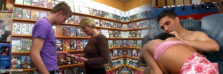 Fabulous blonde mature fucks him in the movie store
