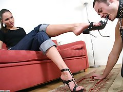 Stunning beauty queen smoking and putting her steel heels into slave's mouth.