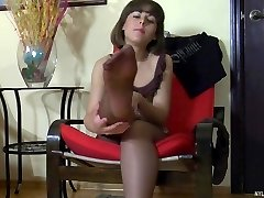 Dolled up hotty exposing her soles in suntan pantyhose right on the sofa